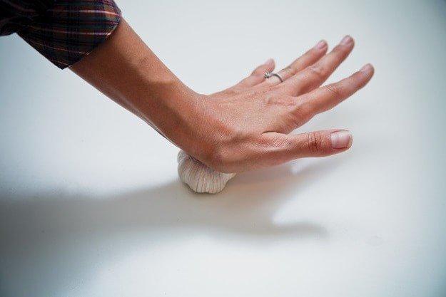 Разделите зубчики раздавив чеснок рукой